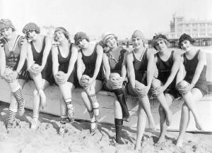 photo_likely_for_arcade_card_mack_sennett_comedies_8_women_in_bathing_suits_and_caps_sitting_on_boat_on_beach.jpg